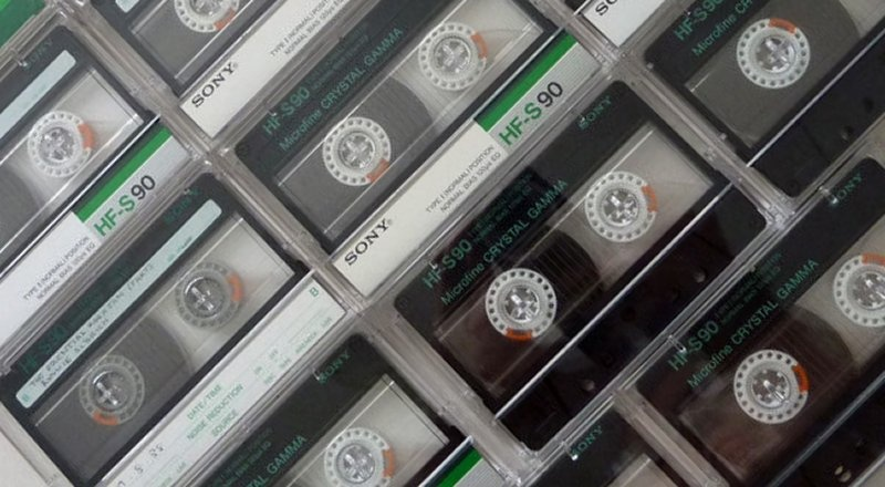 An array of Audio Cassette Tapes are shown side by side in te photo. They are mainly Sony C90 and C60 with their reels rewound, and have green and silver labels.