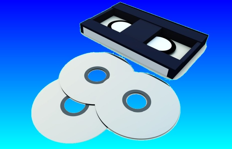A VHS Video tape on its side, together with 3 DVD or CD disks. This is ready to transfer the video from cassette tape to DVD.