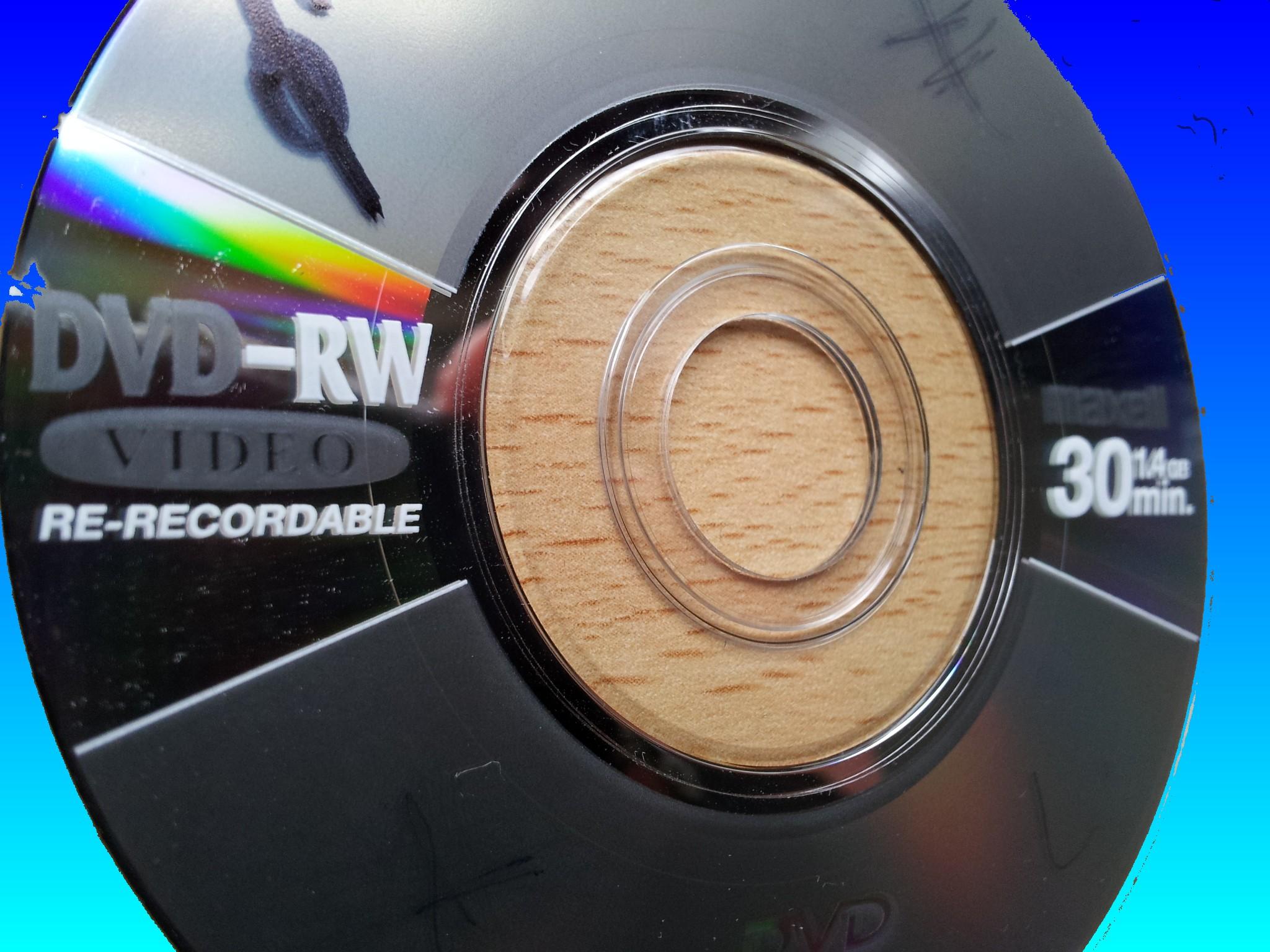 A Maxell DVD-RW in close up image of the label and reflective surface. This disk was used in a Canon Camcorder which failed to finalise the disk and ended with the message Recovering Data Task in progress. Consequently, the disk was later sent to us for recovery of the video.
