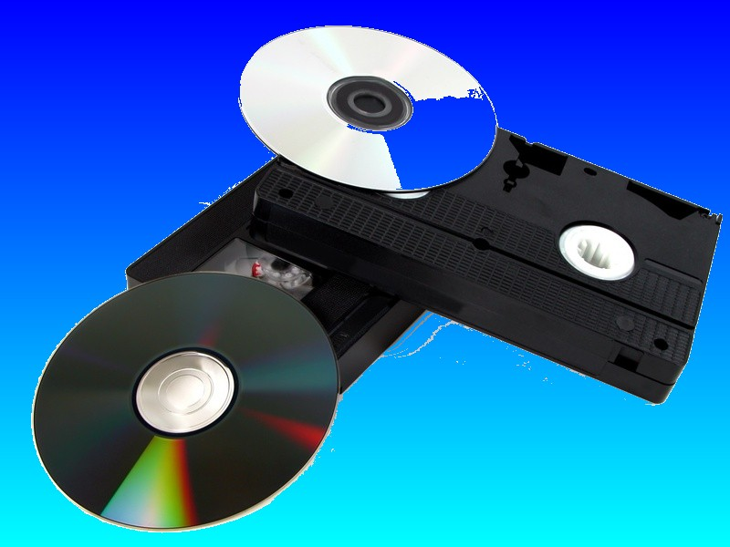 A VHS video tape shown together with some DVD disks ready for transfer of the footage between the vhs cassette and the dvd.