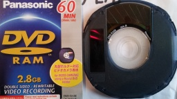 A Panasonic mini DVD-RAM disk 8cm and its cover inlay card. The disk's easily show where video was recorded by the darker inner circle area near the disc centre.