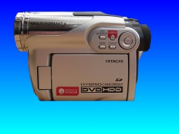 An Hitachi DZ-HS500E DVD HDD hybrid camcorder is pictured in the centre of the image against a blue background. The labels on the camera indicate it uses DVD-RAM disks and an internal hard drive storage for the video data.